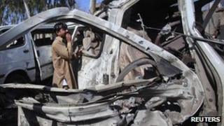 A man cries next to a damaged vehicle, which was hit by a bomb blast, on the outskirts of Peshawar February 23, 2012