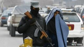 An Afghan policeman keeps watch as a woman pass by a check point in Kabul