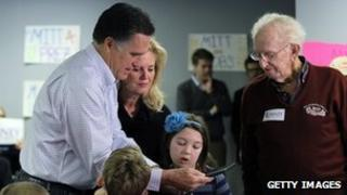 Mitt Romney and his wife Ann look at a photograph of George Romney in Michigan 28 February 2012