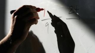 Teacher writing numbers on whiteboard