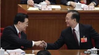 """China's Premier Wen Jiabao, right, shakes hands with President Hu Jintao after the opening ceremony of the National People""""s Congress (NPC) at the Great Hall of the People in Beijing 5 March, 2012"""