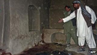 A man points to bloodstains in a room in a house in Alkozai, Kandahar province, Afghanistan, 11 March
