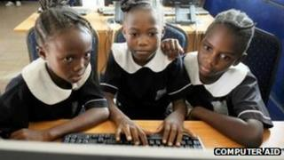 Girls using a computer donated by Computer Aid
