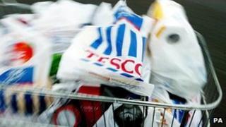 A shopper packs a car with shopping at a Tesco store