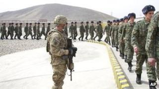 A US soldier watches members of the Afghan Public Protection Force arrive at the transition ceremony of private security forces to Afghan Public Protection Force (APPF) on the outskirts of Kabul