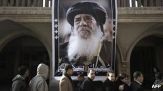 Egyptian Christian Copts wait in a queue next to a poster of Pope Shenouda III at Saint Mark's Coptic Cathedral in Cairo's al-Abbassiya district