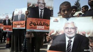 Supporters hold up posters of Abdul Moneim Abu al-Futuh