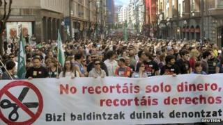 """Protesters in Bilbao carry a banner reading """"You are not just cutting our money, you are cutting our rights"""", 29 March 2012"""