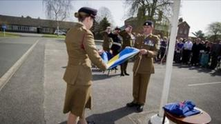 The 5th Division flag is folded as Brigadier Mark Banham, the Lord Lieutenant of Shropshire, and Brigadier David Short, Chief of Staff Support Command, salute.