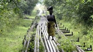 A woman walks along pipelines belonging to Shell in the Niger Delta, Nigeria (Archive shot 2006)