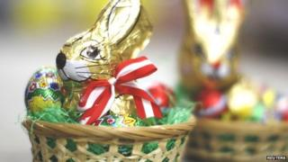 A chocolate Easter rabbit, wrapped in golden foil sits in a bed of green tissue paper, surrounded by little chocolate eggs.