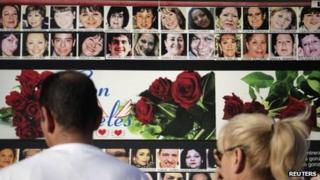 Families look at photographs of the victims on 26 February 2012, six months on from the attack