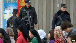 Uighur residents walk past Chinese SWAT policemen standing guard in a street of Yecheng in Xinjiang's Kashgar prefecture, in north west China, 29 Feb 2012