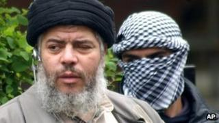Abu Hamza (left) with a masked bodyguard