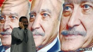 A man walks past election posters for Omar Suleiman in Cairo (6 April 2012)