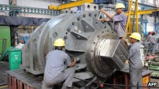 Labourers work on heavy machinery at the in Gujarat state - 28 October 2010