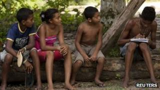 A boy does his homework as others watch in Sao Domingos do Capim March 10, 2012.