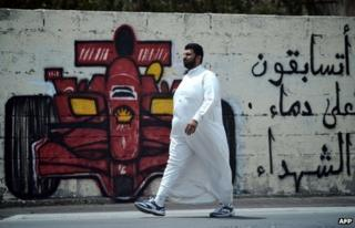 "Man walks past graffiti in Bahrain asking: ""Are you racing on the blood of martyrs?"""