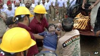 Rescuers remove a worker from the debris of a collapsed factory in Jalandhar on 16 April 2012