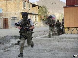 NATO soldiers run during a gun battle in Kabul