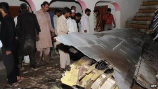 Pakistani villagers look at the plane's wreckage