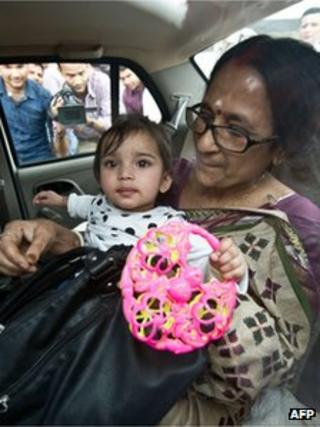 One year old Aishwarya Bhattacharya (C) is held by her grandmother (R) in a car shortly after her arrival at IGI airport in New Delhi on April 24, 2012.