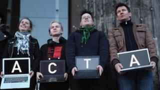 "Protesters hold up laptops spelling out ""Stop Acta"""