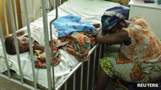 A mother sits next to her daughter who is in hospital with malaria and diarrhoea, 25 April 2012