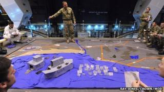 Drill using cardboard boats onboard HMS Illustrious