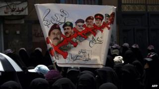 Yemeni women hold a poster demanding the removal of Ali Abdullah Saleh's family from the armed forces (26 April 2012)