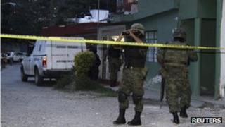 Soldiers patrol the exterior of the house where journalist Regina Martinez lived