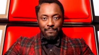 will.i.am in his red chair on the set of The Voice.