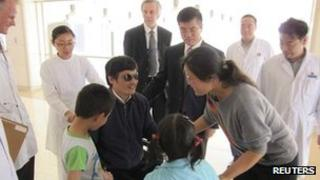 Chen Guangcheng (C) speaks with wife Yuan Weijing (2nd R) and children as US Ambassador Gary Locke (3rd R) and US Assistant Secretary of State for East Asian and Pacific Affairs Kurt Campbell (4th R) stands nearby in a Beijing hospital on 2 May 2012