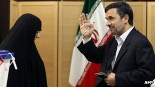 Iranian President Mahmoud Ahmadinejad waves after casting his ballot as his wife Azam Farahi looks on at a polling station for the parliamentary election run-off in Tehran on 4 May 2012.