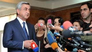 Armenian president Serge Sarkisian speaks with journalists at a polling station in Yerevan