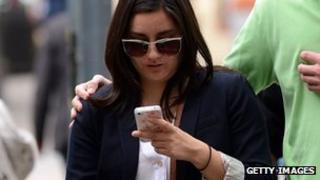 A woman uses a smartphone