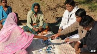 Officials from SKS Microfinance receive payment from a borrower
