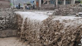 A mudstream washes down through a village in Gansu province, 11 May 2012