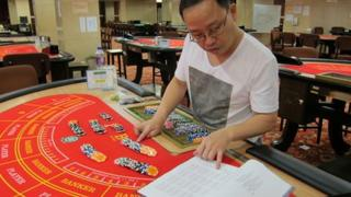 Ng Hoi Wing calculates chip payouts on hands of Baccarat