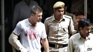 Australian batsman Luke Pomersbach is escorted by Indian policemen to be produced at a court in New Delhi, India, Friday, May 18, 2012.