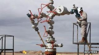 A worker measures the pressure and temperature of an oil and gas production tree October 14 2011