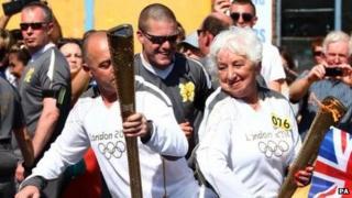 Marlene Barnett passes the Olympic flame on in the relay through Newport