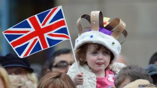 A young girl wears a homemade crown as she waits to see Queen Elizabeth II visit the town centre of Accrington as part of the Queen's Diamond Jubilee tour of the country on 16 May 2012