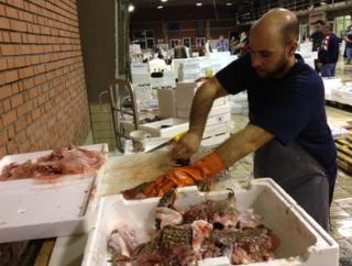 A man cleans fish in a market in Kavala, northern Greece