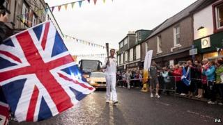 Torchbearer Ross McClelland carries the Olympic flame through Stranraer