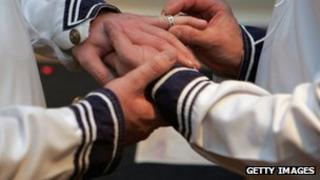 A man putting a wedding ring on another man's hand