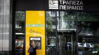 A woman withdraws money from a branch of Piraeus bank in central Athens on May 17