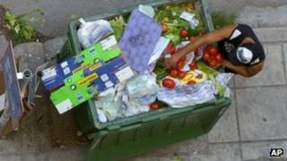 A man searches for food in a bin in Thessaloniki, Greece, 5 June