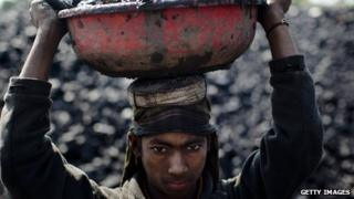 Young boy carrying coal at a mine in India