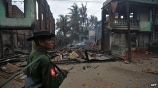 A Burmese soldier patrols past destroyed houses in Sittwe June 14 2012